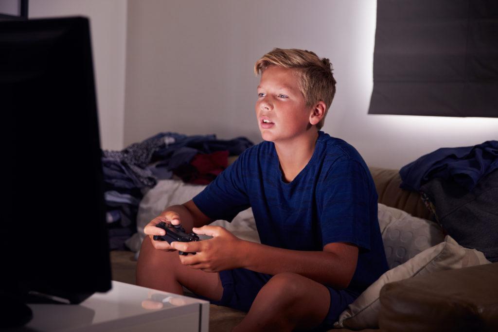 Teenage Boy Gaming At Home