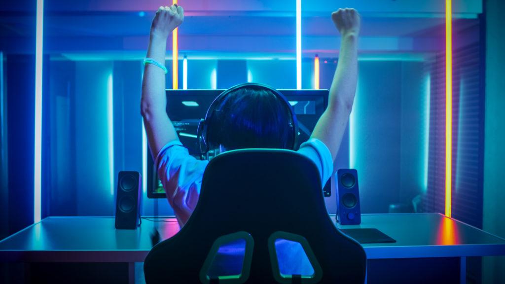Nuori mies hehkuttaa onnistumistaan tietokoneruudun edessä.